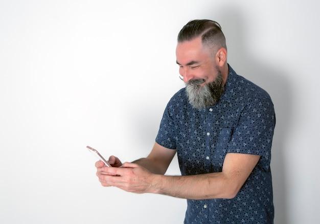 Bebaarde man die een smiley maakt kijken naar zijn smartphone geïsoleerd op een witte achtergrond white