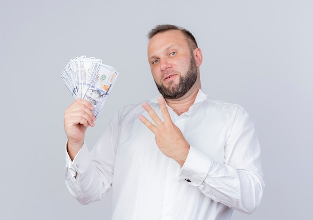 Bebaarde man die een wit overhemd draagt dat contant geld toont en met vingers omhoog wijst nummer drie glimlachend zelfverzekerd over witte muur