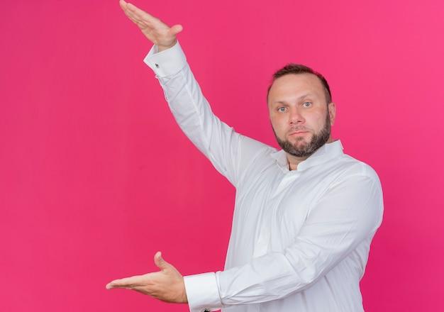 Bebaarde man die een wit overhemd draagt dat groot formaatgebaar met de maatregel van het handensymbool toont die zich over roze muur bevindt