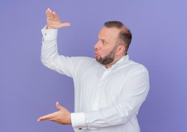 Bebaarde man die een wit overhemd draagt dat groot formaatgebaar met handen toont die verbaasd en verbaasd symboolmaatregel kijken die zich over blauwe muur bevindt