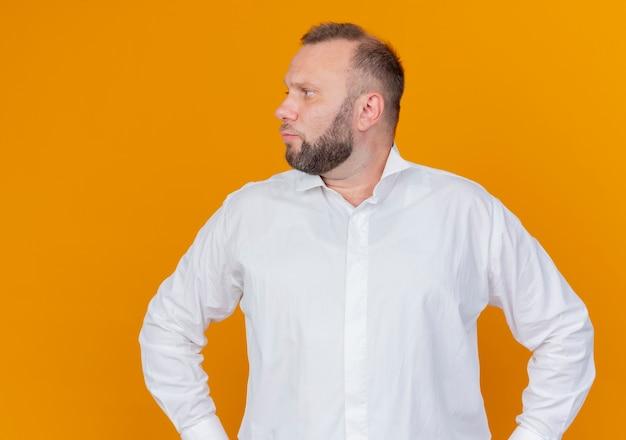 Bebaarde man die een wit overhemd draagt dat opzij kijkt met een ernstig gezicht dat zich over oranje muur bevindt