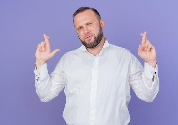 Bebaarde man die een wit overhemd draagt dat wenselijke wens maakt die vingers kruist die zich over blauwe muur bevinden