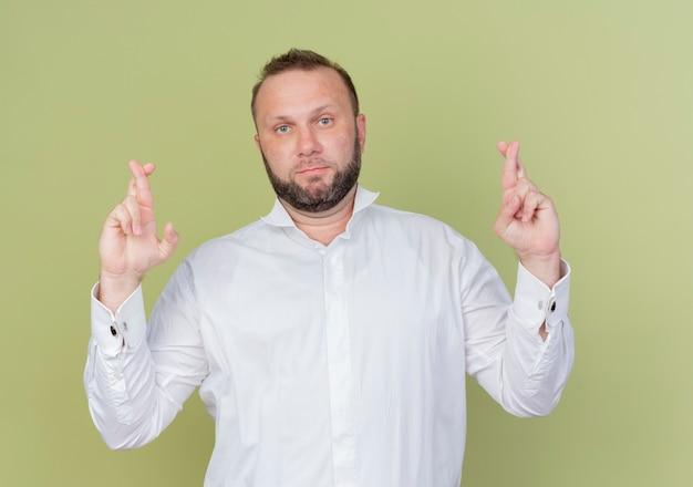 Bebaarde man die een wit overhemd draagt dat wenselijke wens maakt die vingers kruist die zich over lichte muur bevinden