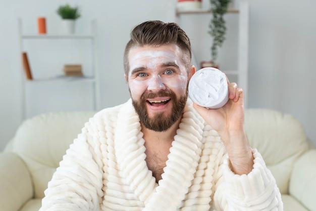 Bebaarde man die gezichtscrème aanbrengt voor spiegel huidverzorging en spa voor man concept