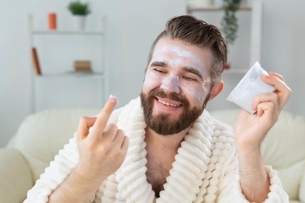 Bebaarde man die gezichtscrème voor spiegel aanbrengt huidverzorging en spa voor man concept.