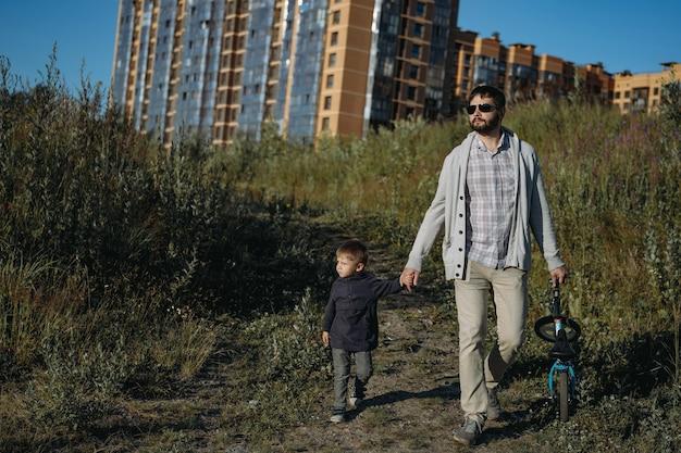 Bebaarde man die heuvelafwaarts loopt en een schattig zoontje met de hand vasthoudt en een runbike in een andere hand