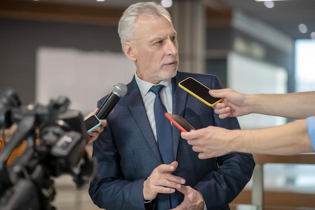 Bebaarde man die ontevreden kijkt naar de persconferentie