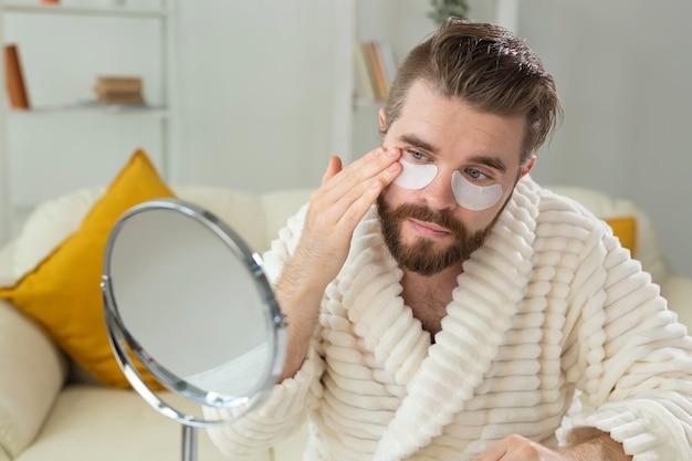 Bebaarde man die ooglapjes op zijn gezicht aanbrengt rimpels en gezichtsverzorging voor mannen