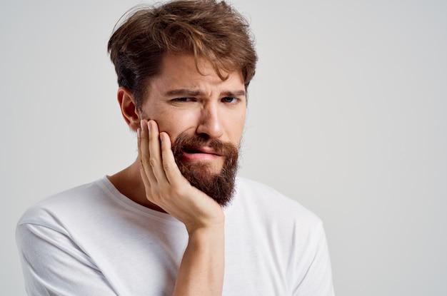 Bebaarde man die vasthoudt aan de pijn in tanden geïsoleerde achtergrond