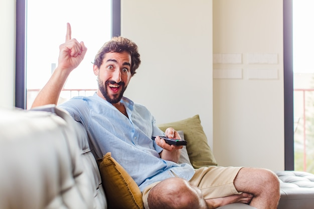 Bebaarde man die zich als een gelukkig en opgewonden genie voelt na het realiseren van een idee, opgewekt de vinger opstekend, eureka!