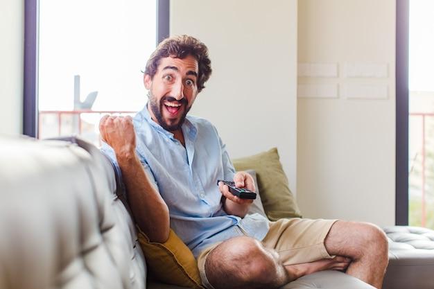 Bebaarde man die zich geschokt, opgewonden en gelukkig voelt, lacht en succes viert, zegt wauw!