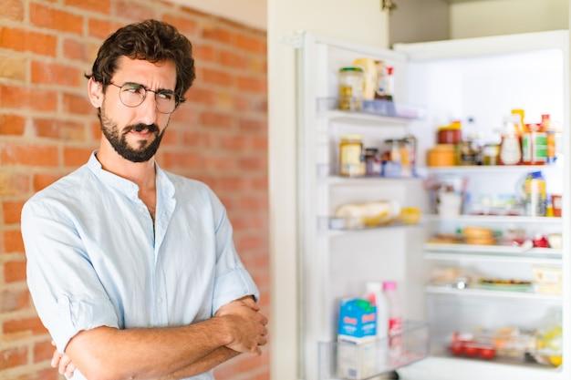 Bebaarde man die zich verdrietig, overstuur of boos voelt en opzij kijkt met een negatieve houding, fronsend bij onenigheid