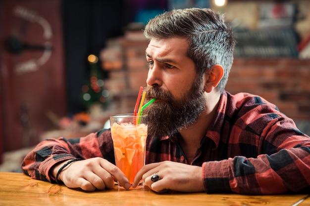 Bebaarde man drinkt cocktail. knappe kapper die bij pub rust. bebaarde brutale hipster-denken.