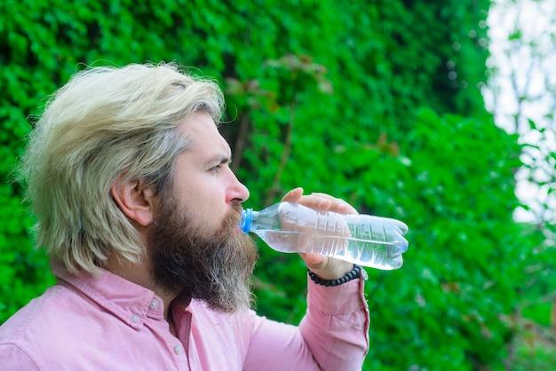 Bebaarde man drinkwater hydratatie concept aqua uitdroging man drink water buiten man met water