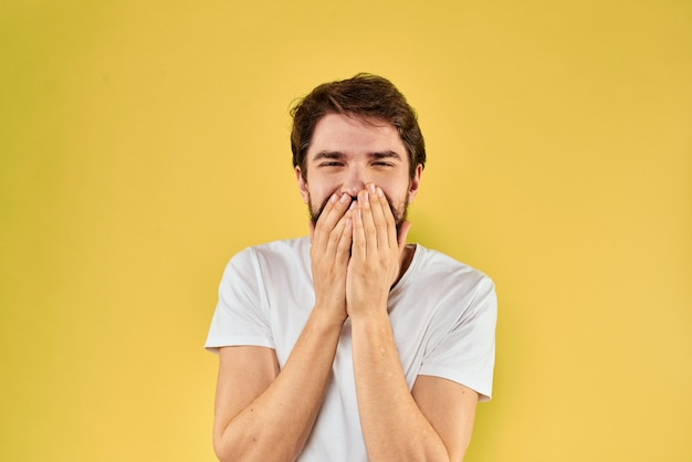 Bebaarde man emoties leuk gebaar met handen wit t-shirt close-up gele achtergrond. hoge kwaliteit foto