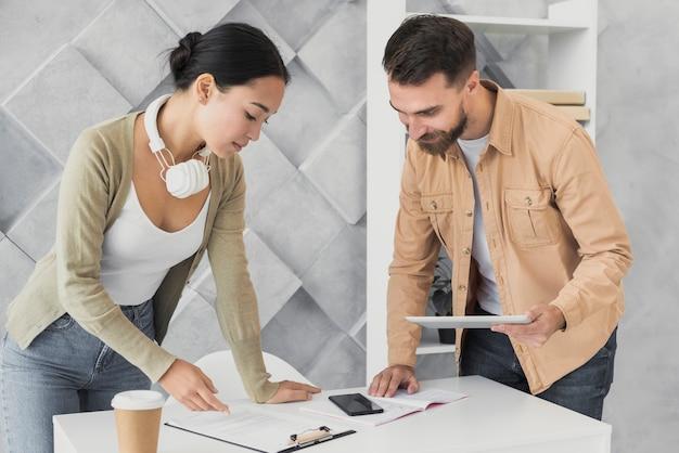 Bebaarde man en aziatische vrouw die op het klembord kijken