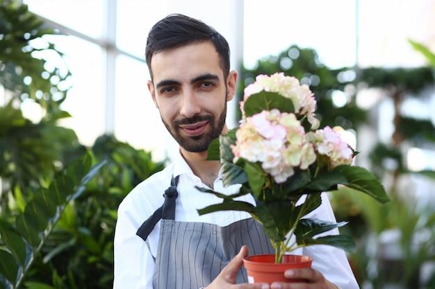 Bebaarde man gardener holding white flower in pot