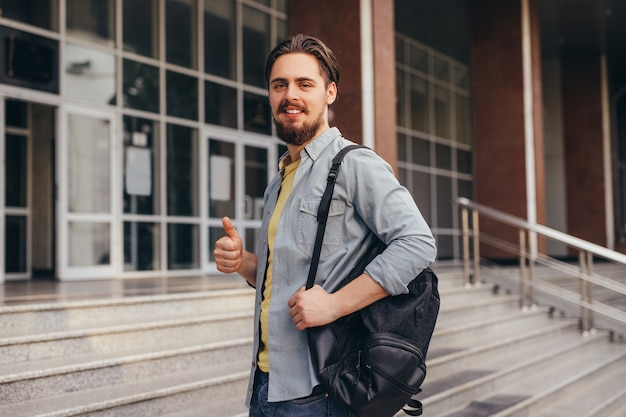 Bebaarde man gebaren duim omhoog tijdens het solliciteren op de universiteit