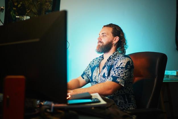 Bebaarde man gebruikt computer tegen groenblauw licht zittend op een stoel