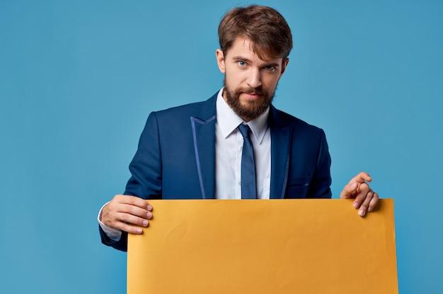 Bebaarde man gele mockup poster in de hand blauwe achtergrond