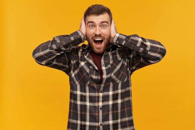Bebaarde man, gelukkig uitziende man met donkerbruin haar. een geruit overhemd en accessoires dragen. emotie concept. bedek oren met palmen, geïsoleerd over gele muur