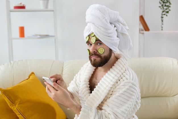 Bebaarde man geniet met een cosmetisch masker op zijn gezicht gemaakt van plakjes komkommer mannen huidverzorging en