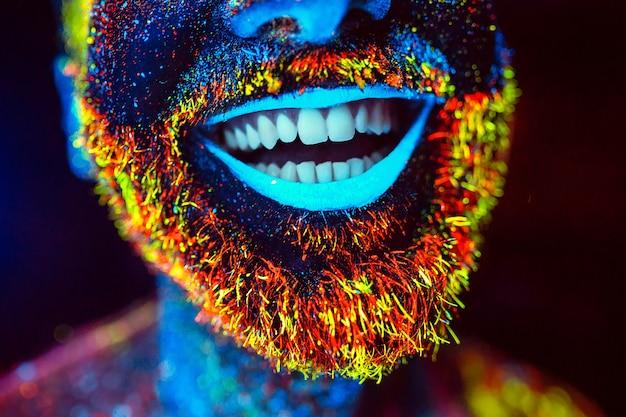 Bebaarde man geschilderd in fluorescerend poeder