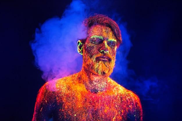 Bebaarde man geschilderd in fluorescerende poeder met rook.