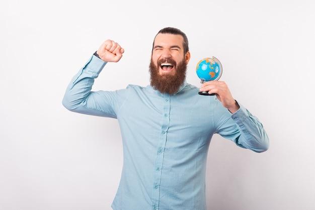 Bebaarde man heeft een reis gewonnen en maakt het winnaarsgebaar terwijl hij een earth globe vasthoudt.