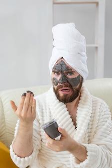 Bebaarde man heeft een schone, frisse huid, draagt een schoonheidskleimasker op het gezicht en geniet van schoonheidsbehandelingen in de spa