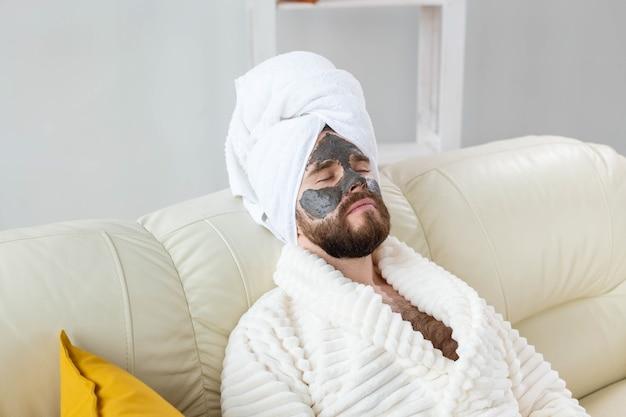 Bebaarde man heeft een schone, frisse huid, draagt een schoonheidskleimasker op het gezicht en geniet van schoonheidsbehandelingen. spa thuis, lichaams- en huidverzorging.
