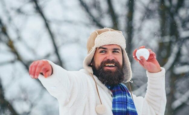 Bebaarde man het gooien van een sneeuwbal buiten
