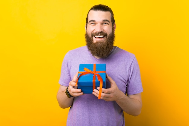 Bebaarde man houdt een klein blauw verpakt cadeau op gele achtergrond.