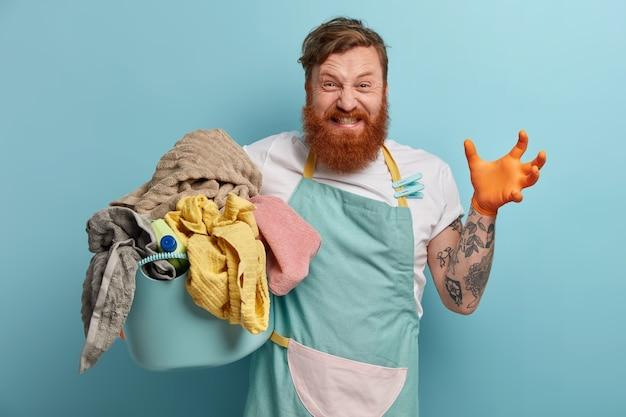 Bebaarde man houdt wasmand vast, overweldigd door huishoudelijke taken