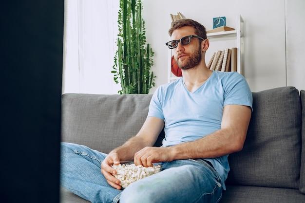 Bebaarde man in 3d-bril zittend op de bank en kijken naar film met popcorn thuis