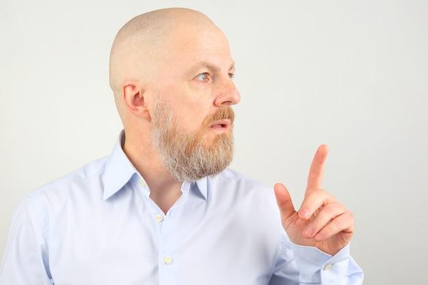 Bebaarde man in blauw shirt toont wijsvinger