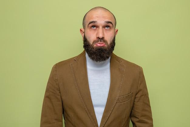 Bebaarde man in bruin pak kijkt verward en verbaasd op