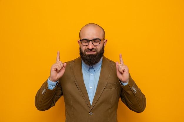 Bebaarde man in bruin pak met bril blij en positief wijzend met wijsvingers omhoog