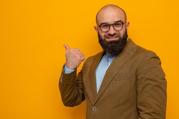 Bebaarde man in bruin pak met een bril die er gelukkig en positief uitziet en vrolijk glimlacht, wijzend terug met duim