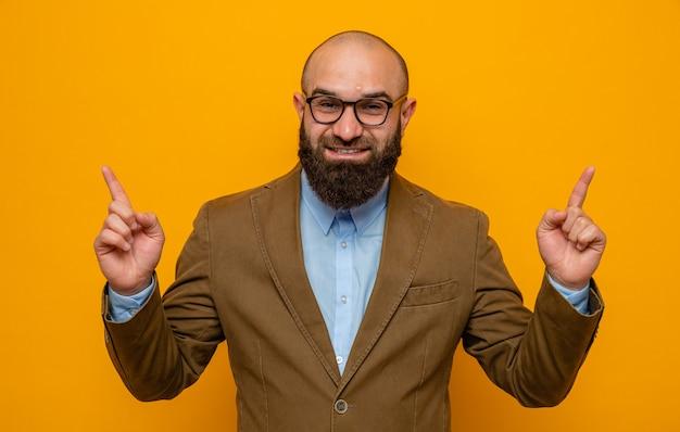 Bebaarde man in bruin pak met een bril die er gelukkig en positief uitziet, wijzend met de wijsvingers omhoog