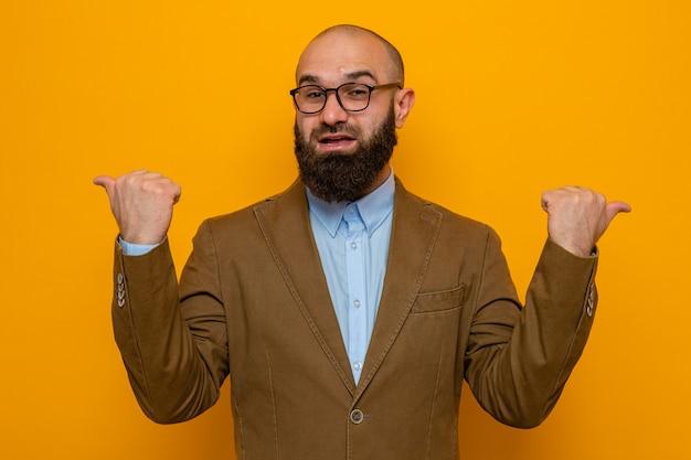 Bebaarde man in bruin pak met een bril die er verward uitziet en glimlacht, wijzend met duimen