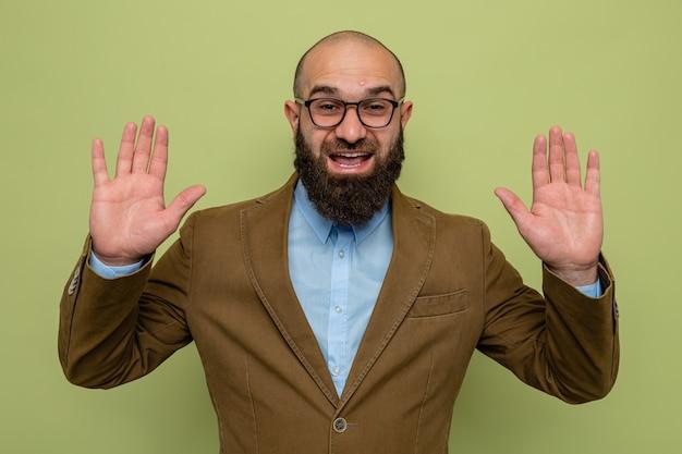 Bebaarde man in bruin pak met een bril die naar de camera kijkt, blij en opgewonden, zijn armen opstekend over een groene achtergrond