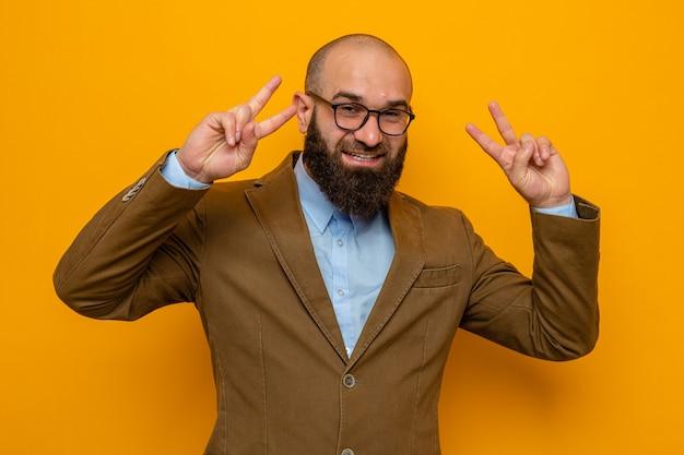 Bebaarde man in bruin pak met een bril die naar de camera kijkt, blij en vrolijk glimlacht, vrolijk met een v-teken dat over een oranje achtergrond staat