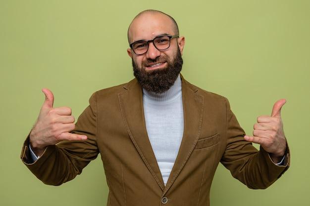 Bebaarde man in bruin pak met een bril die naar de camera kijkt en vrolijk glimlacht en laat zien dat je me een gebaar over een groene achtergrond laat zien