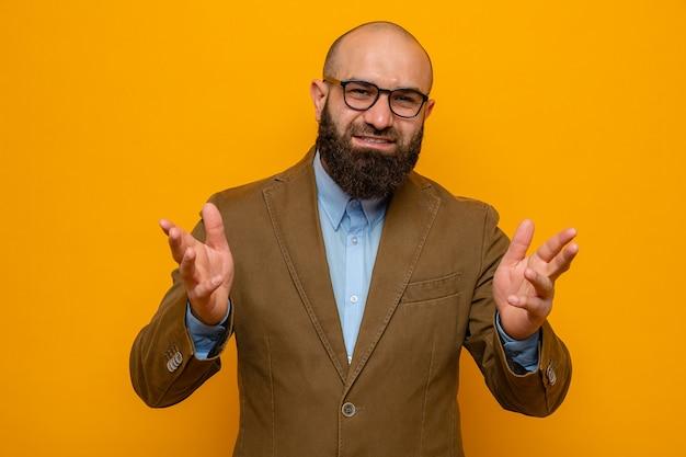 Bebaarde man in bruin pak met een bril die naar de camera kijkt, gelukkig en positief glimlacht en vrolijk zijn armen opheft over oranje achtergrond