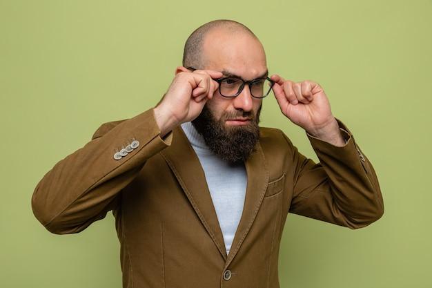 Bebaarde man in bruin pak met een bril die opzij kijkt en zijn bril nauw aanraakt die over een groene achtergrond staat