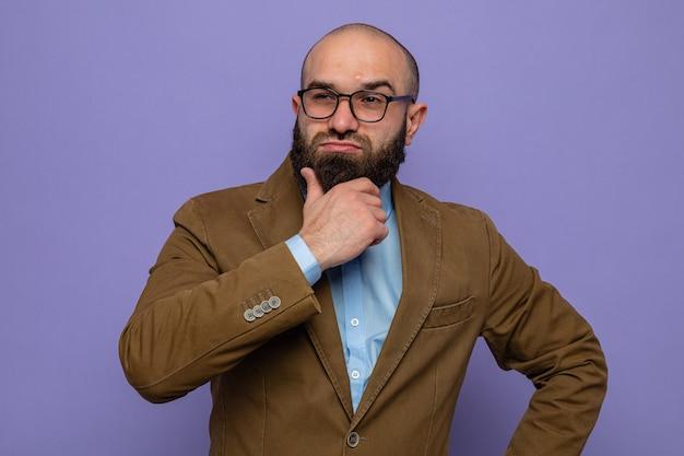 Bebaarde man in bruin pak met een bril die opzij kijkt met een peinzende uitdrukking over een paarse achtergrond