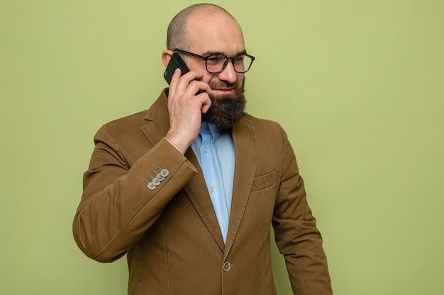 Bebaarde man in bruin pak met een bril die vrolijk glimlacht terwijl hij op een mobiele telefoon praat die over een groene achtergrond staat