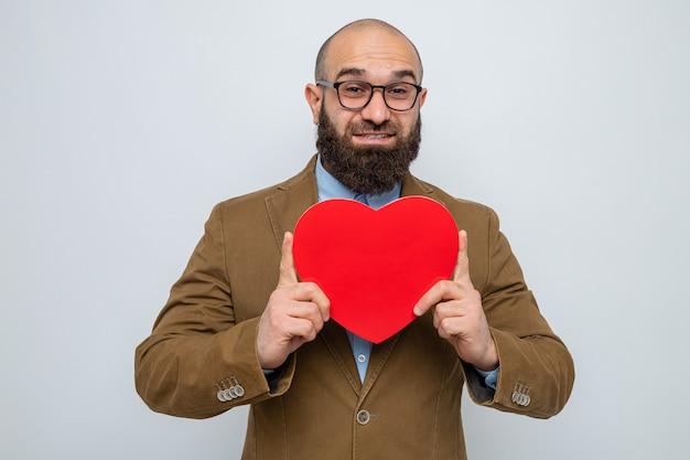 Bebaarde man in bruin pak met een bril met een hart gemaakt van karton en glimlachend vrolijk gelukkig en positief