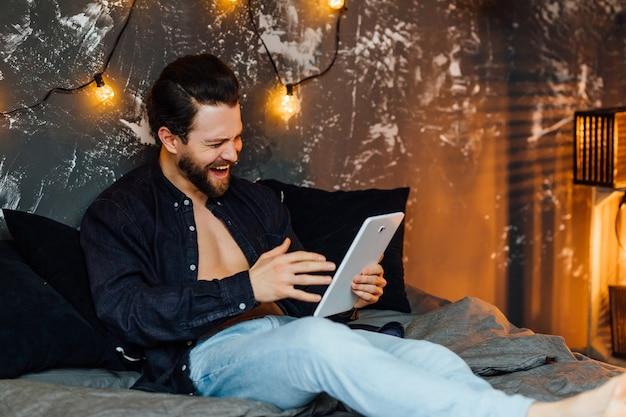 Bebaarde man in de ochtend, liggend op bed met tablet en glimlachend in moderne badkamer.